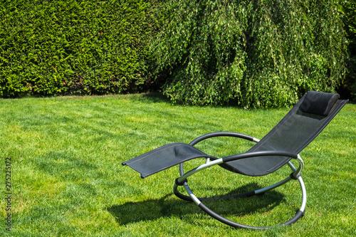 Obraz na plátne Rocking lounger on a green grass. Summer time. Copy space