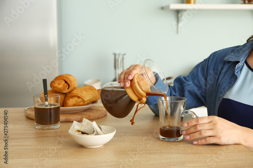 Photo Woman pouring tasty coffee from chemex into cup at table