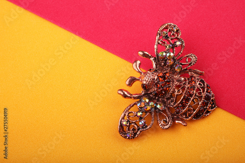 Beautiful brooch in the form of a fly on a yellow background Fototapete
