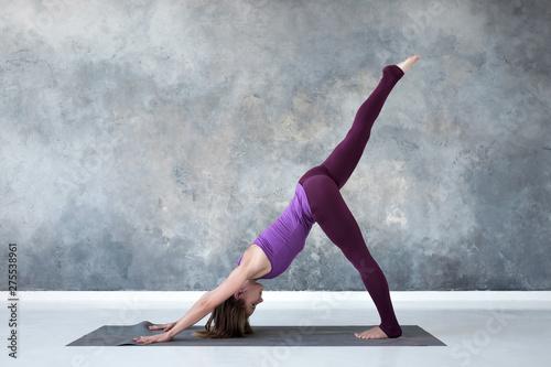 Slika na platnu Slim european woman doing yoga exercise downward facing dog pose or eka pada adho mukha svanasana