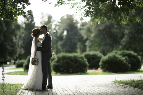 Foto Kissing in the park the bride and groom newlyweds