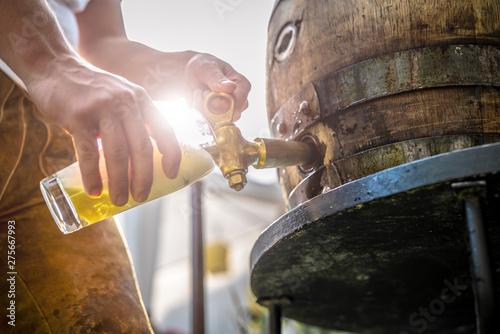 Tableau sur Toile bayerischer Mann in Lederhose sticht ein Holzfass Bier im Garten an und genießt