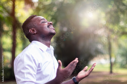 Fototapeta African man praying for thank god with light flare in the green nature