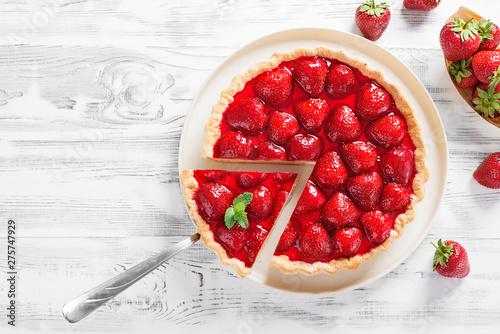 Fotografia Delicious strawberry tart on white wooden background, top view