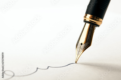Foto golden fountain pen leaves a signature on a white paper