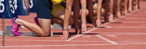 Photo Group of male track athletes on starting blocks
