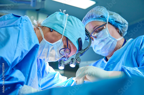 Obraz na plátně A surgeon's team in uniform performs an operation on a patient at a cardiac surgery clinic