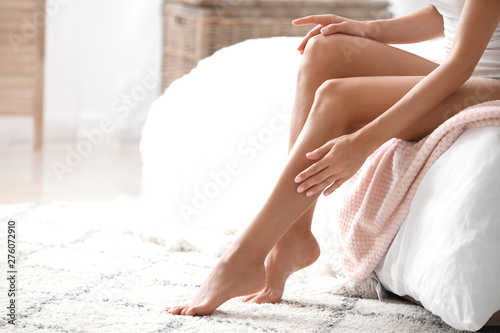 Fototapeta Young woman with beautiful legs in bedroom
