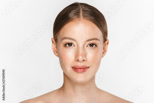 Valokuvatapetti Beautiful young woman with healthy glowy skin posing isolated over white wall background
