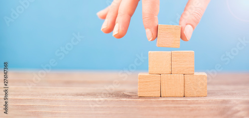 Fotografia woman is placing blank blocks in a row on the blue background