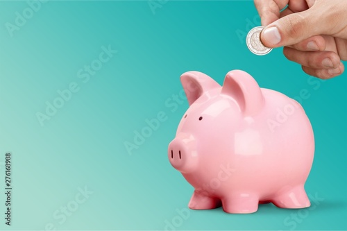 Fotografija Man putting coin in pig moneybox