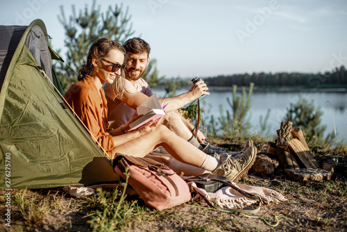 Fotografia Young and cheerful couple having a picnic at the campsite while traveling in the