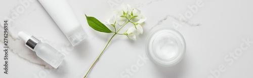 Fotografia panoramic shot of jasmine, cosmetic glass bottle, jar with cream and moisturizer