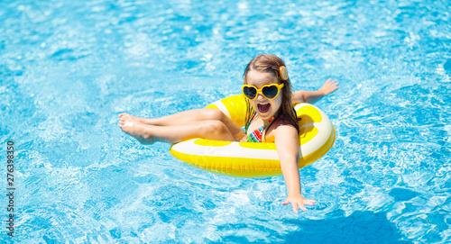 Fényképezés Child in swimming pool on ring toy. Kids swim.