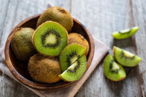 Fotografia Fresh kiwi fruit in the bowl on wooden background