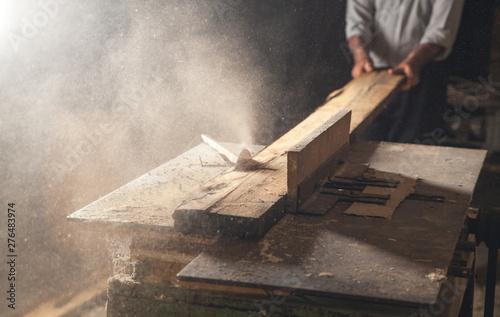 Carpenter cutting a wooden plank with a carpentry machine. Fototapet