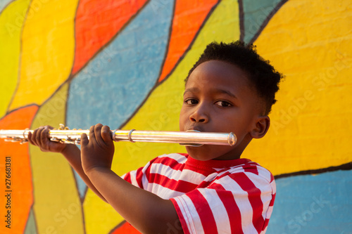 Schoolboy playing flute instrument in the school playground