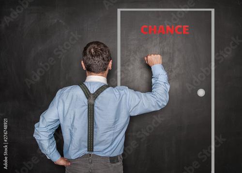 Leinwand Poster Business man knock by fist on door blackboard