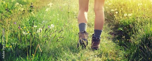 Obraz na płótnie Young woman hiker walking on trail in grassland