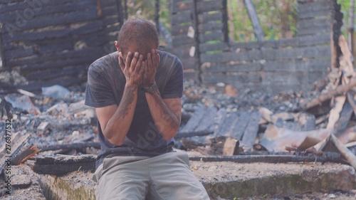 Fotografie, Obraz Portrait of a sad man on the background of a burned house, after fire