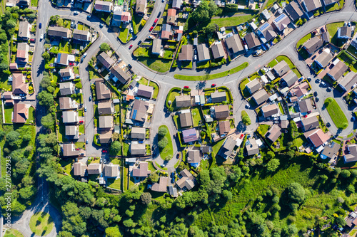 Leinwand Poster Aerial drone view of small winding sreets and roads in a residential area of a s