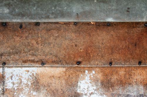 Tło w stylku wabi-sabi: brązowa płyta z gwoździami pokryta łuszczącą się białą farbą