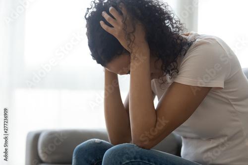 Valokuva Sad hopeless black woman sit alone at home feeling depressed