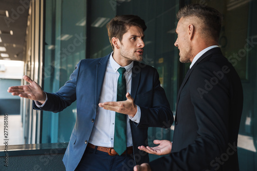 Carta da parati Image of aggressive businessmen partners talking and discussing conflict while s