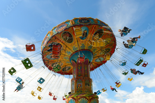 Foto June 10, 2018: Children ride on the carousel in an amusement park against a blue sky