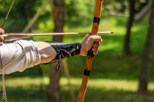 Archer hand holds his bow with an arrow and aiming at the target outdoor activity in forest Fototapeta