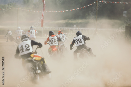 Photo Racing motorcycles making a lot of dust when accelerating after the turn on the dirt racing track