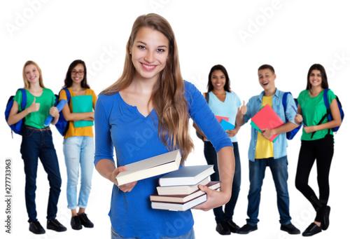 Photo Sympathische blonde Studentin mit Büchern und Gruppe internationaler Studenten