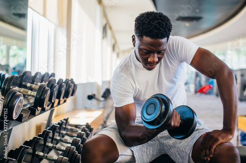 Photo Young African American man sitting and lifting a dumbbell close to the rack at gym