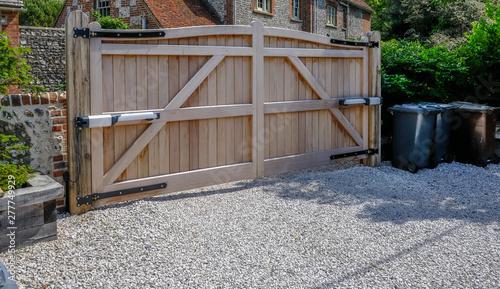 Obraz na płótnie Large wooden entry electric gates with stone driveway.