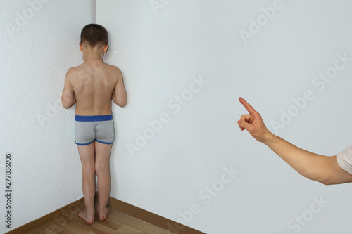 Carta da parati punished boy, a junior schoolboy, standing in a corner undressed, facing the wal