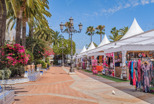 Fotografie, Tablou One of the main pretty squares in Ayamonte, Spain during the summer when there are stores selling clothes, sweets and souvenirs