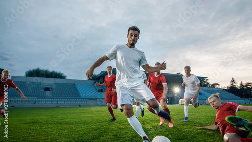 Photo Professional Soccer Player Outruns Members of Opposing Team and Kicks Ball to Score Goal