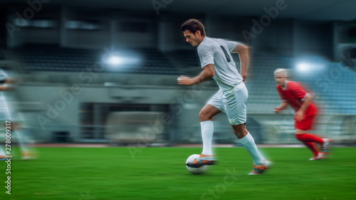 Fotografia Blurred Motion Shot of Professional Soccer Player Leads with a Ball