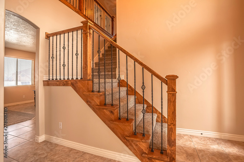 Canvas Print Carpeted stairs with wood handrail and metal railing inside an empty new home