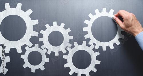 Obraz na płótnie Business operation. Businessman drawing gears on chalkboard.