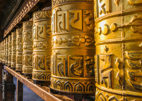 Stampa su Tela A prayer wheels on a spindle made from metal and wood