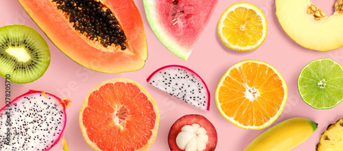 Creative layout made of papaya, grapefruit, lemon, kiwi, melon, watermelon, banana, pineapple, orange, mangosteen and flowers on pink background.  Tropical flat lay. Summer fruits concept.
