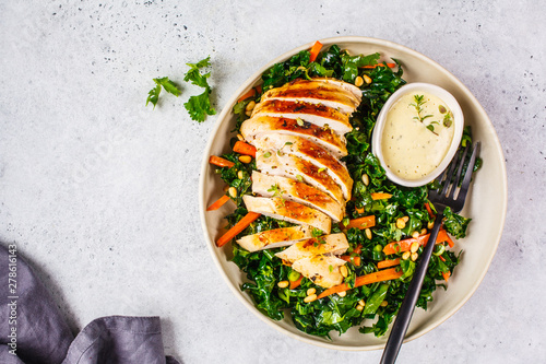 Fotografia Grilled chicken breast salad with kale, pine nuts and caesar dressing in a white plate