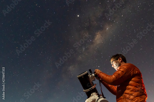 Foto One astronomer man looking the night sky through an amateur telescope and taking