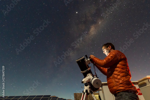 Leinwand Poster One astronomer man looking the night sky through an amateur telescope and taking