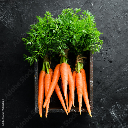 Fotomural Fresh carrots on a black stone background
