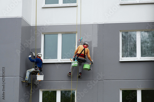 Canvas Print Worker hanging on rope and paints building wall with roller