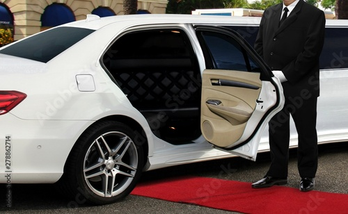 Fotografia Chauffeur driver standing next to limo opened car door with red carpet