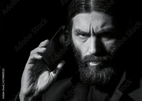 Carta da parati strange bearded senior priest with a smartphone, bearded old man is calling on a dark background