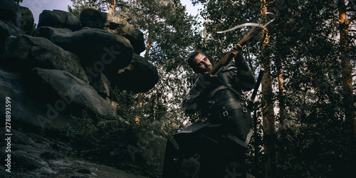 Fotografia Mystery scarface knight in armor with sword and crossbow in the forest